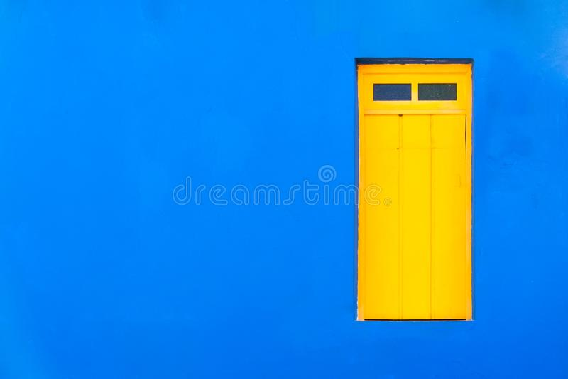 La fachada azul del estilo tropical del Caribe colonial colorido cerró la ventana en un fondo azul brillante e intenso de la casa imágenes de archivo libres de regalías