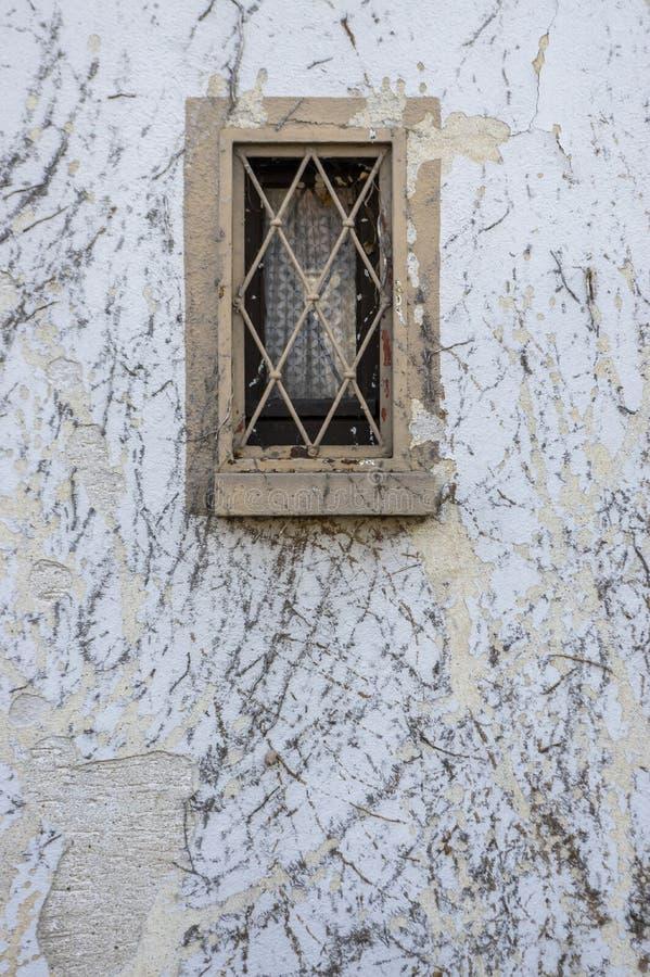 La fachada con los restos de la vegetación de la hiedra común es dañada por el yeso y las ventanas de madera del pintura y pequeñ foto de archivo libre de regalías