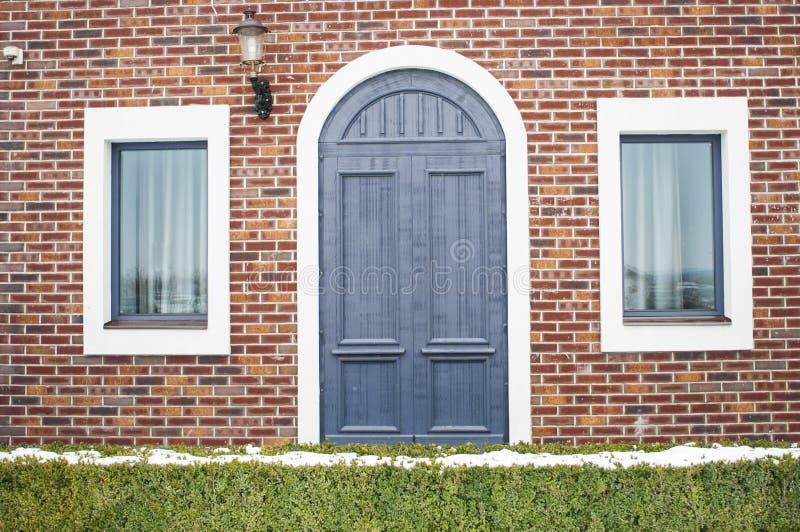 La fachada de la casa con un azul arqueó la puerta imagenes de archivo