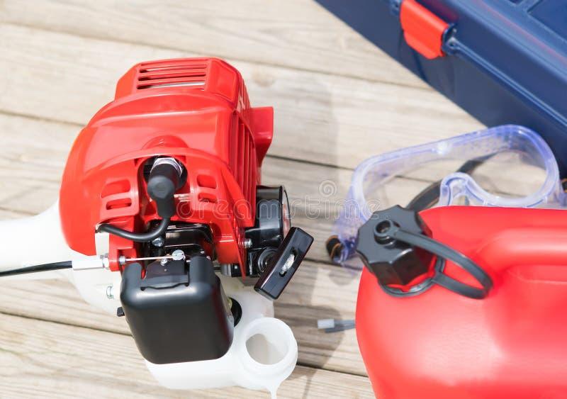 La falciatrice e una scatola metallica rossa con benzina e gli strumenti si trovano su un fondo di legno immagini stock libere da diritti