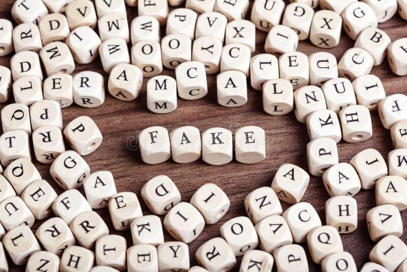 La falsificazione, lettera taglia la parola a cubetti immagini stock libere da diritti
