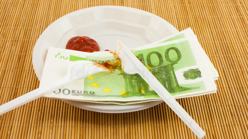 La fame per soldi, 100 tovaglioli degli euro, ketchup, la forcella di plastica ed il coltello fotografie stock libere da diritti