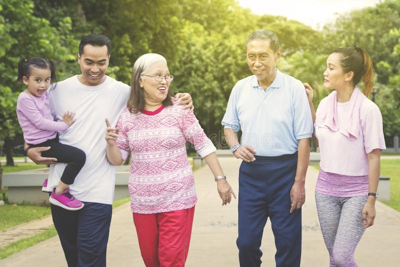 La famiglia allargata felice cammina insieme nel parco immagini stock libere da diritti