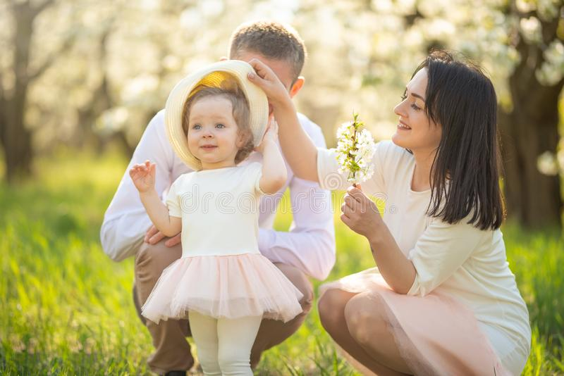 La famiglia allegra cammina nel parco con i raggi del sole Giardini di fioritura di umore di primavera fotografia stock libera da diritti