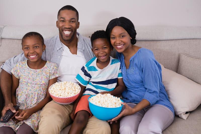 La famiglia allegra con popcorn lancia ubicazione sul sofà immagine stock