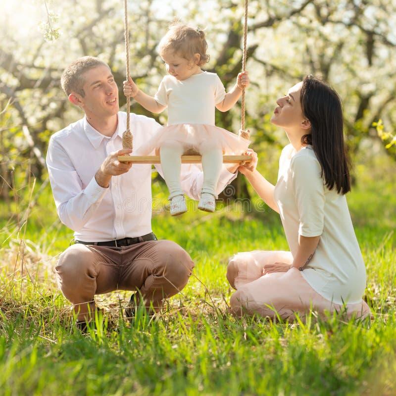 La famiglia allegra scuote un bambino su un'oscillazione, in un giardino fiorito o in un parco Calorosamente, umore di amore, del fotografia stock