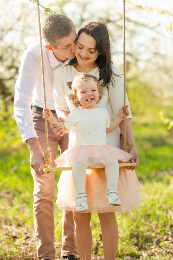 La famiglia allegra scuote un bambino su un'oscillazione, in un giardino fiorito o in un parco Calorosamente, umore di amore, del fotografia stock libera da diritti