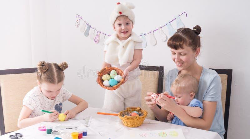 La famiglia celebra Pasqua: La mamma ed i bambini dipingono le uova di Pasqua alla tavola fotografia stock