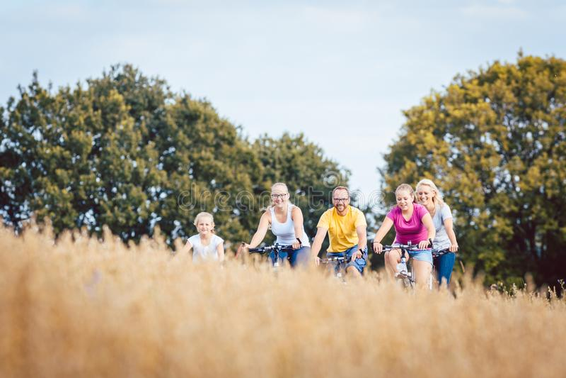La famiglia che guida le loro bici ha sparato sopra un campo di grano fotografia stock libera da diritti