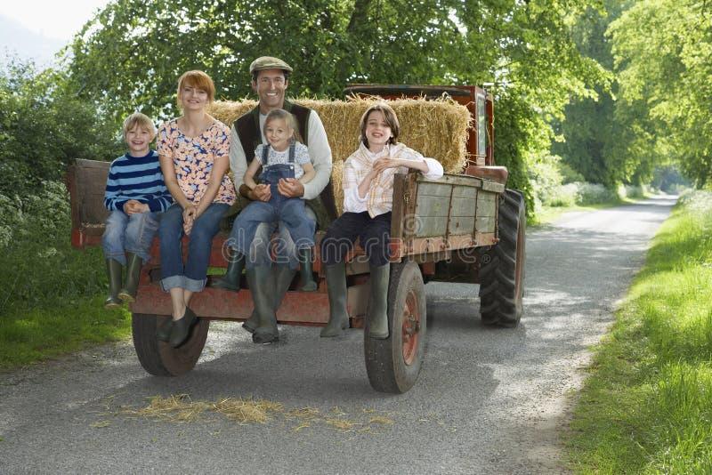 La famiglia che si siede sopra appoggia del rimorchio sul vicolo del paese fotografie stock libere da diritti