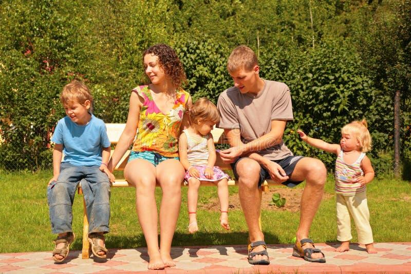 la famiglia cinque del banco si siede fotografia stock