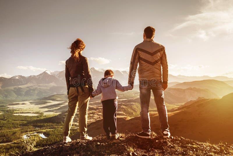 La famiglia con il figlio sta il tramonto delle montagne immagine stock