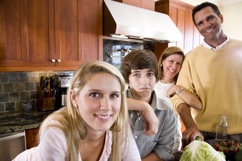 La famiglia con l'adolescente scherza in cucina, ragazzo che aggrotta le sopracciglia fotografie stock libere da diritti