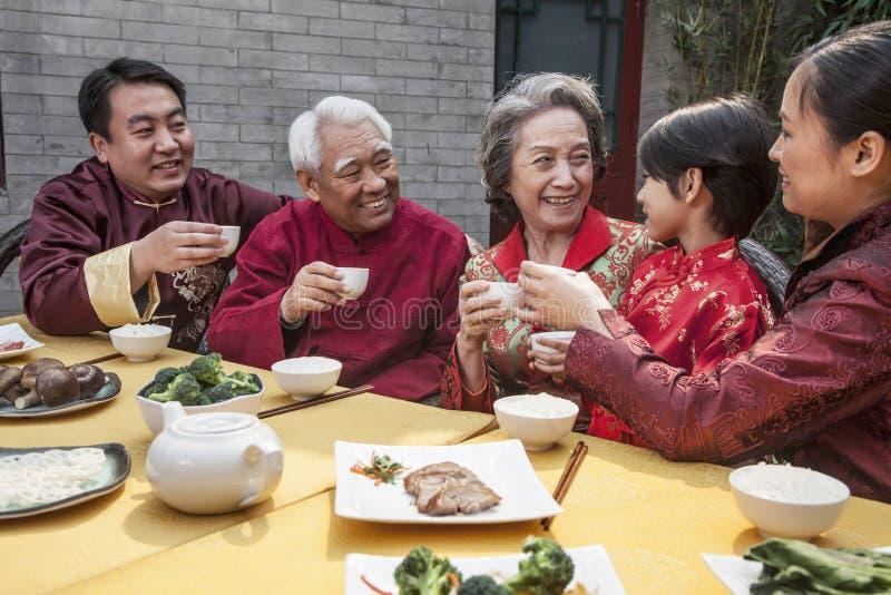 La famiglia con le tazze ha sollevato la tostatura sopra un pasto cinese fotografia stock