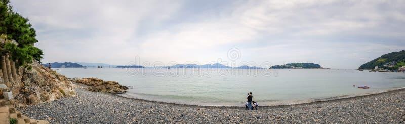 La famiglia coreana gode della vista della spiaggia di pietra dei ciottoli neri e grigi di colore immagini stock libere da diritti