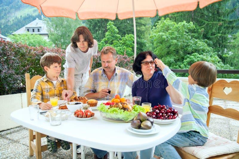 La famiglia da cinque persone ha la cena sul terrazzo dell'estate fotografia stock libera da diritti
