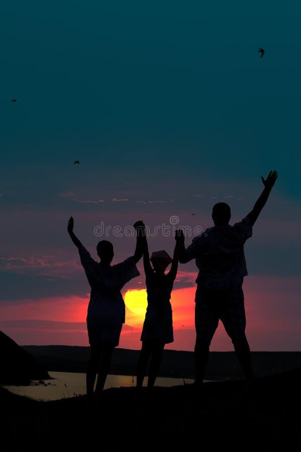 La famiglia da tre persone accoglie favorevolmente il tramonto fotografia stock libera da diritti