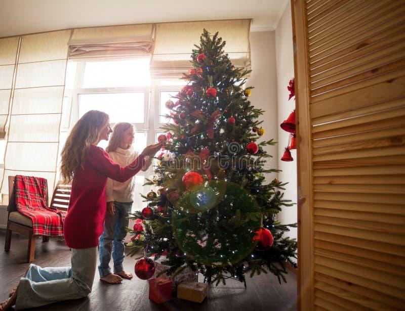 La famiglia decora l'albero di Natale immagine stock