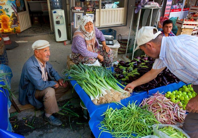 La famiglia degli anziani vende le erbe, le cipolle ed i peperoni da un'azienda agricola sul mercato del villaggio in Turchia fotografia stock libera da diritti