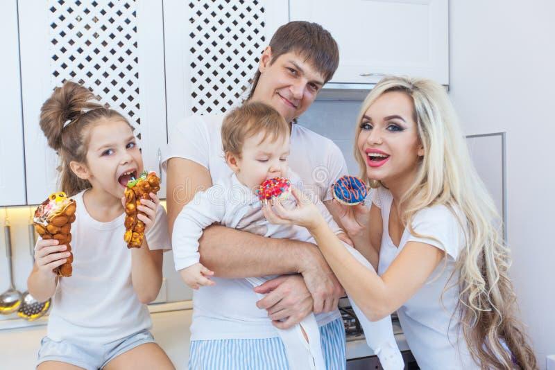 La famiglia di quattro divertente sui precedenti della cucina luminosa bei si diverte imbrogliando intorno il cibo delle guarnizi fotografie stock libere da diritti