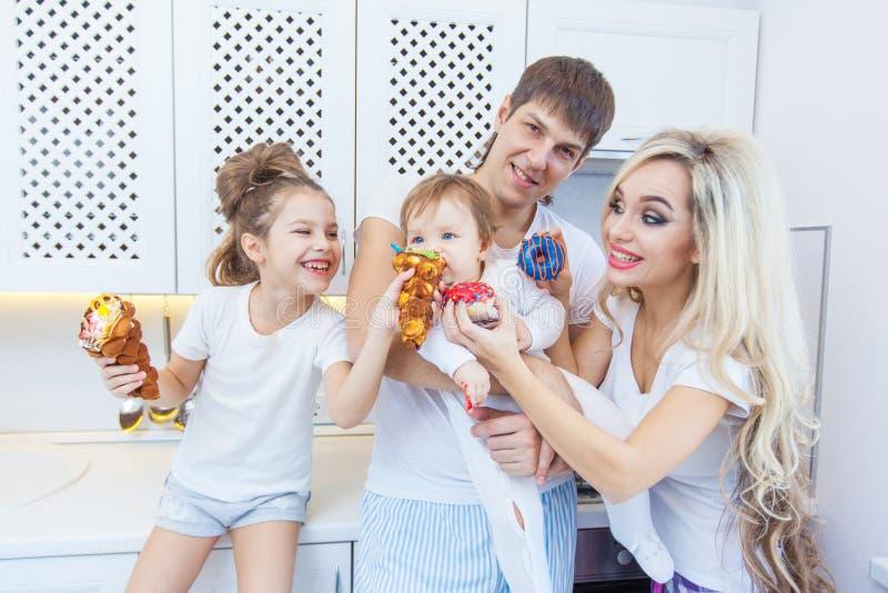 La famiglia di quattro divertente sui precedenti della cucina luminosa bei si diverte imbrogliando intorno il cibo delle guarnizi immagini stock
