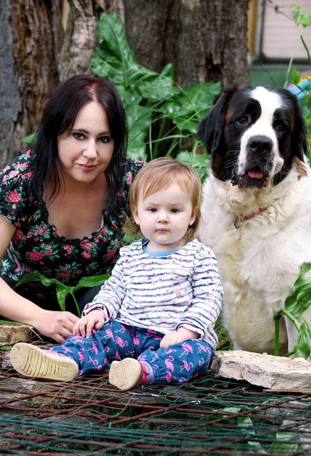 La famiglia e l'amore pets il ritratto di concetto con la madre e la neonata è sedentesi e giocante con il cane in giardino all'a immagini stock libere da diritti