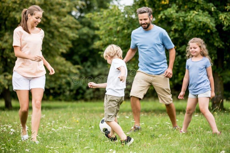 La famiglia ed i bambini giocano a calcio immagine stock
