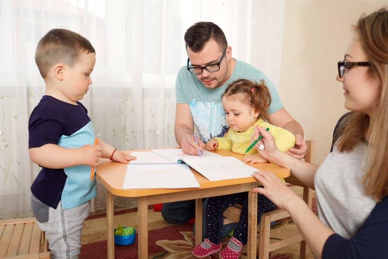La famiglia estrae le matite ad una tavola nella sala immagini stock