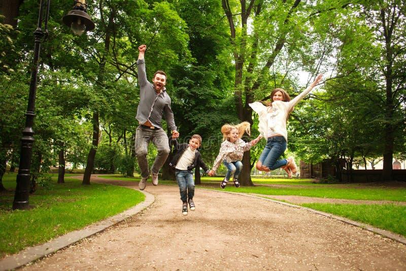 La famiglia felice allegra nel parco dell'estate che salta insieme si diverte fotografia stock libera da diritti