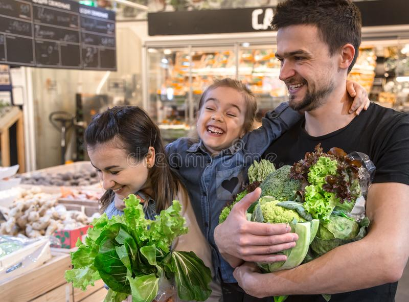 La famiglia felice compra le verdure Una famiglia allegra di tre pomodori di scelta nel dipartimento di verdure del supermercato  fotografie stock