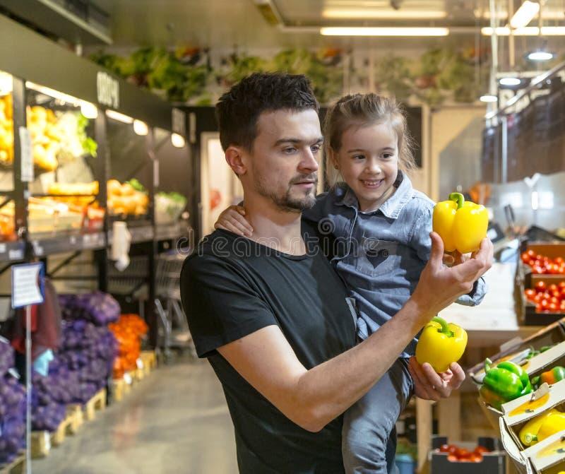 La famiglia felice compra le verdure Una famiglia allegra di tre pomodori di scelta nel dipartimento di verdure del supermercato  immagine stock libera da diritti