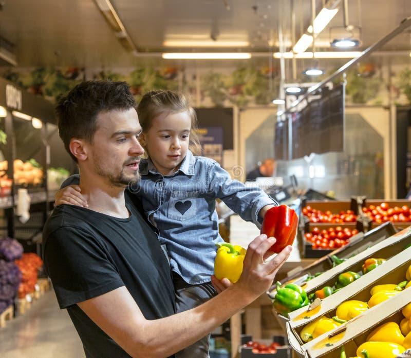La famiglia felice compra le verdure Una famiglia allegra di tre pomodori di scelta nel dipartimento di verdure del supermercato  fotografia stock libera da diritti