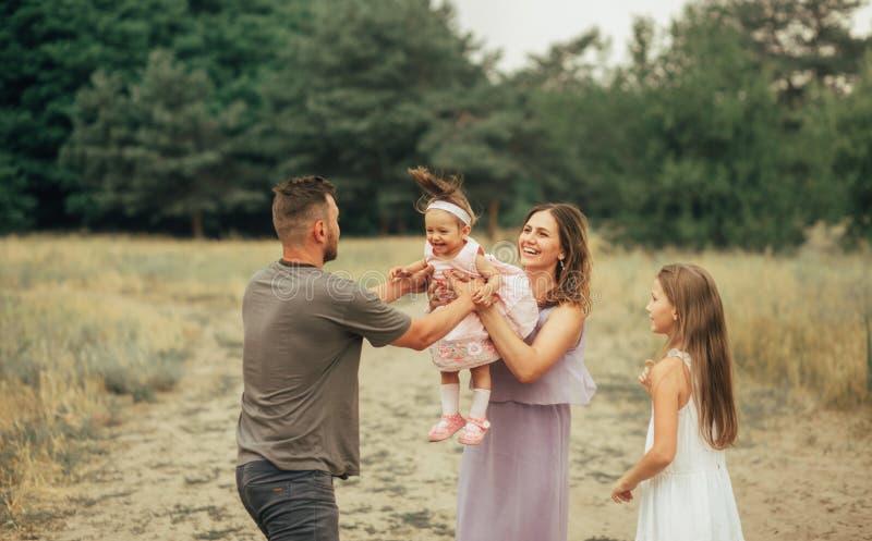 La famiglia felice con due bambini si diverte e ride su una passeggiata immagini stock libere da diritti