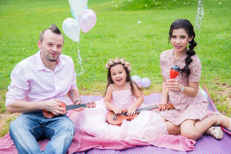 La famiglia felice con una figlia che gioca la musica e canta una canzone immagini stock libere da diritti