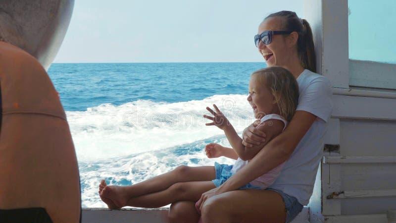 La famiglia felice della madre e la piccola figlia sveglia scattano sulla barca fotografia stock libera da diritti