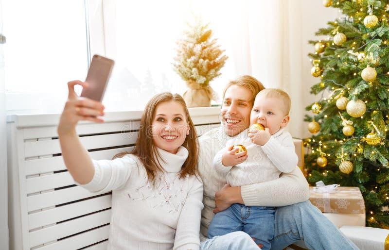 La famiglia felice fotografata sul telefono, fa i selfies nel Natale m. immagine stock libera da diritti
