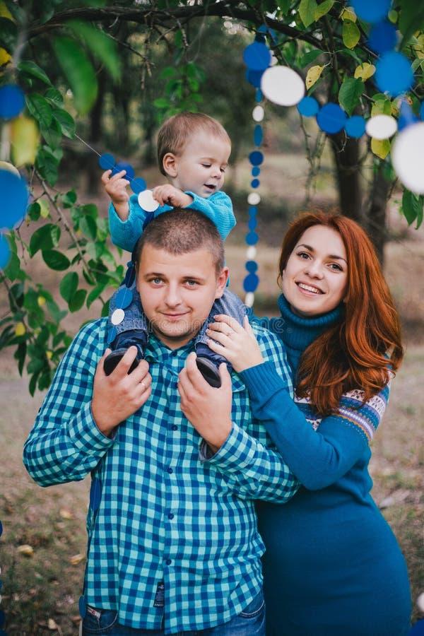 La famiglia felice ha festa di compleanno con le decorazioni blu in foresta immagini stock