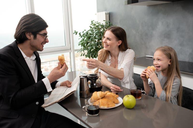 La famiglia felice ha una prima colazione a casa immagini stock libere da diritti