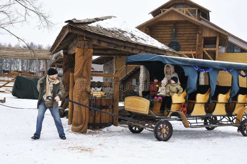 La famiglia felice in inverno spende il carrello di guida di tempo fotografia stock libera da diritti