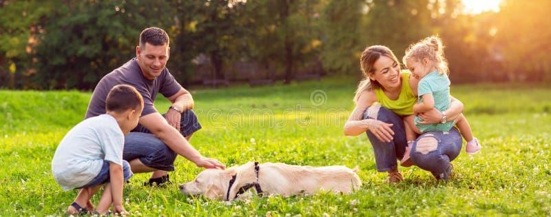 La famiglia felice sta divertendosi con il golden retriever - playin della famiglia immagine stock