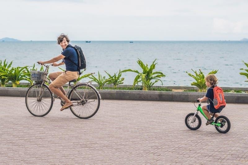 La famiglia felice sta guidando le bici all'aperto e sorridere Padre su una b immagini stock