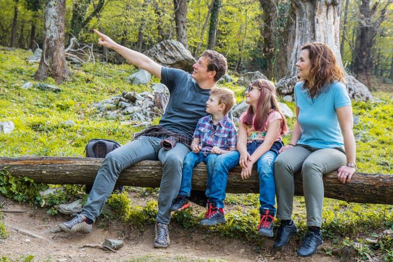 La famiglia felice sta sedendo sul tronco di un albero in una foresta immagine stock libera da diritti