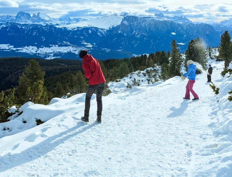 La famiglia gioca alle palle di neve sul pendio di montagna dell'inverno fotografie stock