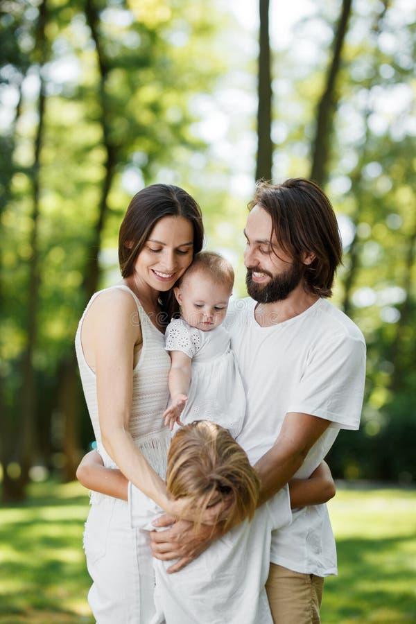 La famiglia graziosa ed amichevole sta avendo resto nel parco Il papà e la mamma stanno tenendo la figlia nelle armi e nell'abbra fotografia stock libera da diritti