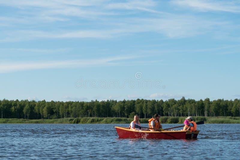 La famiglia guida una barca di legno sul lago in buon tempo sulla vacanza, feste attive immagini stock libere da diritti