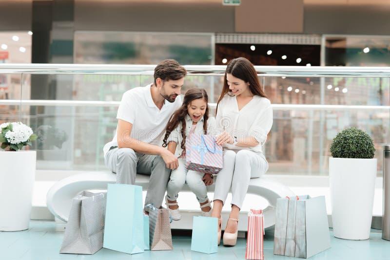 La famiglia, il padre, la madre e la figlia stanno sedendo sul banco nel centro commerciale La ragazza sta guardando dentro una b immagine stock