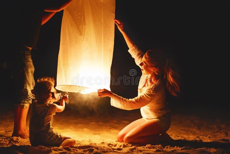 La famiglia invia ad aria la lampada celeste della torcia elettrica in volo sulla spiaggia immagini stock libere da diritti