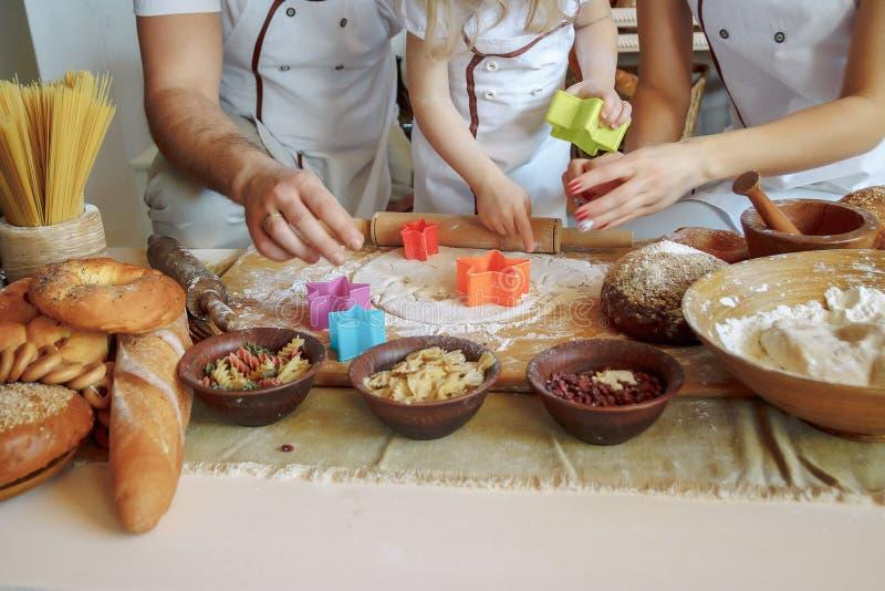 La famiglia nella cucina produce i biscotti, taglierine del biscotto, pasta Classe matrice Prodotti della farina forno immagine stock
