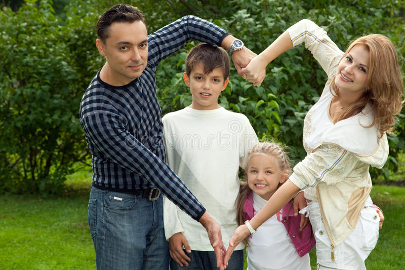 la famiglia passa il cuore che fa all'aperto il simbolo immagine stock libera da diritti
