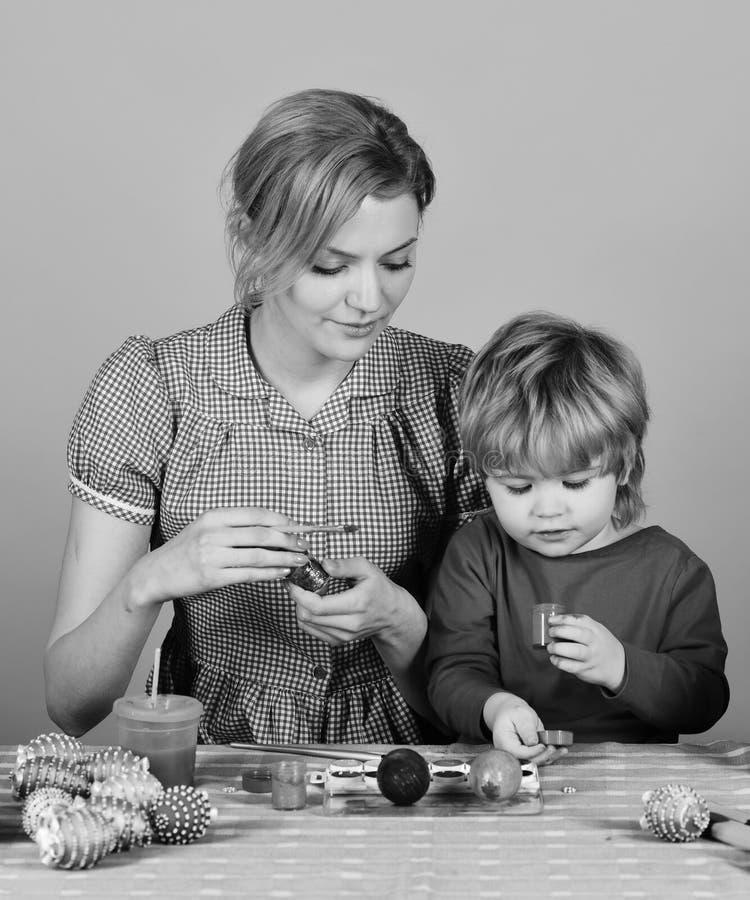 La famiglia prepara per la festa Uova della pittura del figlio e della madre immagini stock